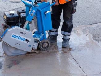 Bauarbeiter schneidet Fliesen und macht Lärm
